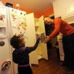 Skokie's Jason Lancaster takes cereal from his daughter, Mary, 2, for their new pantry. The Lancasters will start the new year with a reorganized home after winning a $25,000 interior makeover from Chicago Closets by Design. | Ryan Pagelow~Sun-Times Media