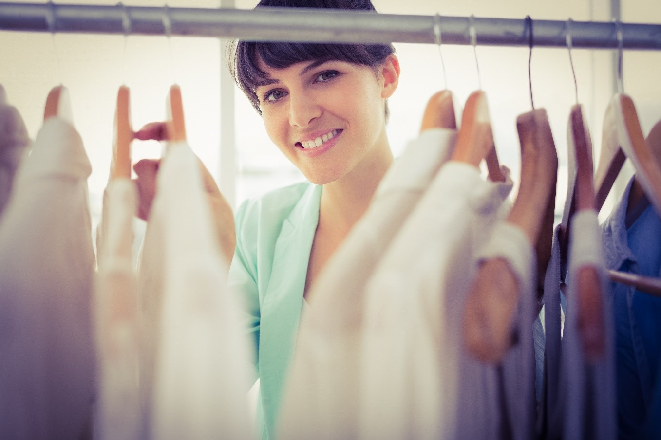 A woman in front of an organized custom closet.