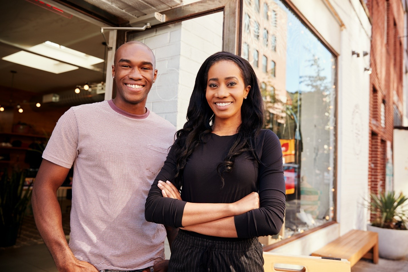 A married African-American couple standing in front of their business.