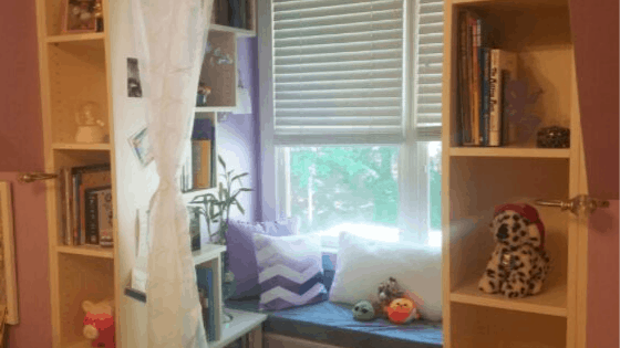 A child's bedroom organized with a reading nook and a bench.