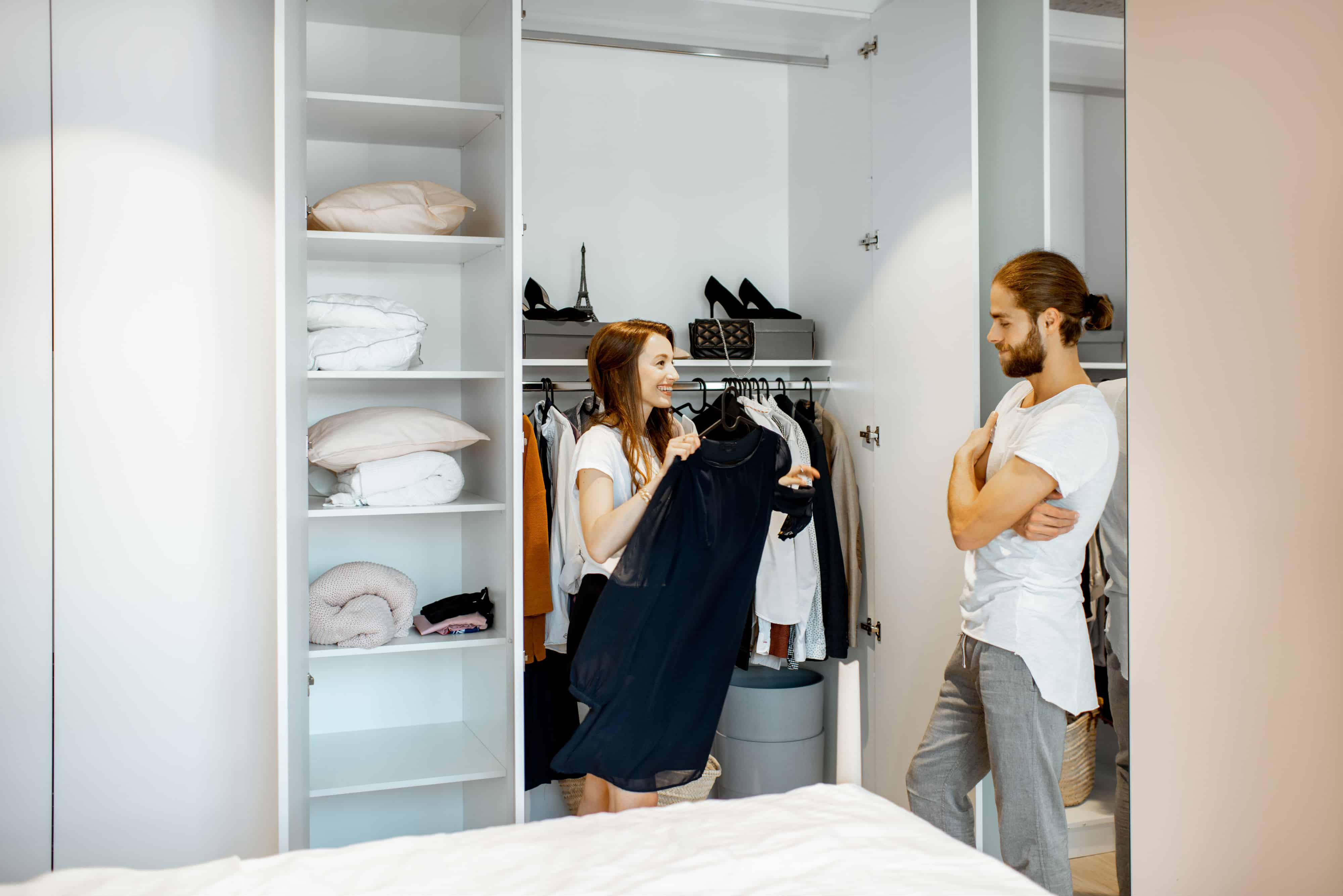A couple in front of their custom closet picking what to wear.