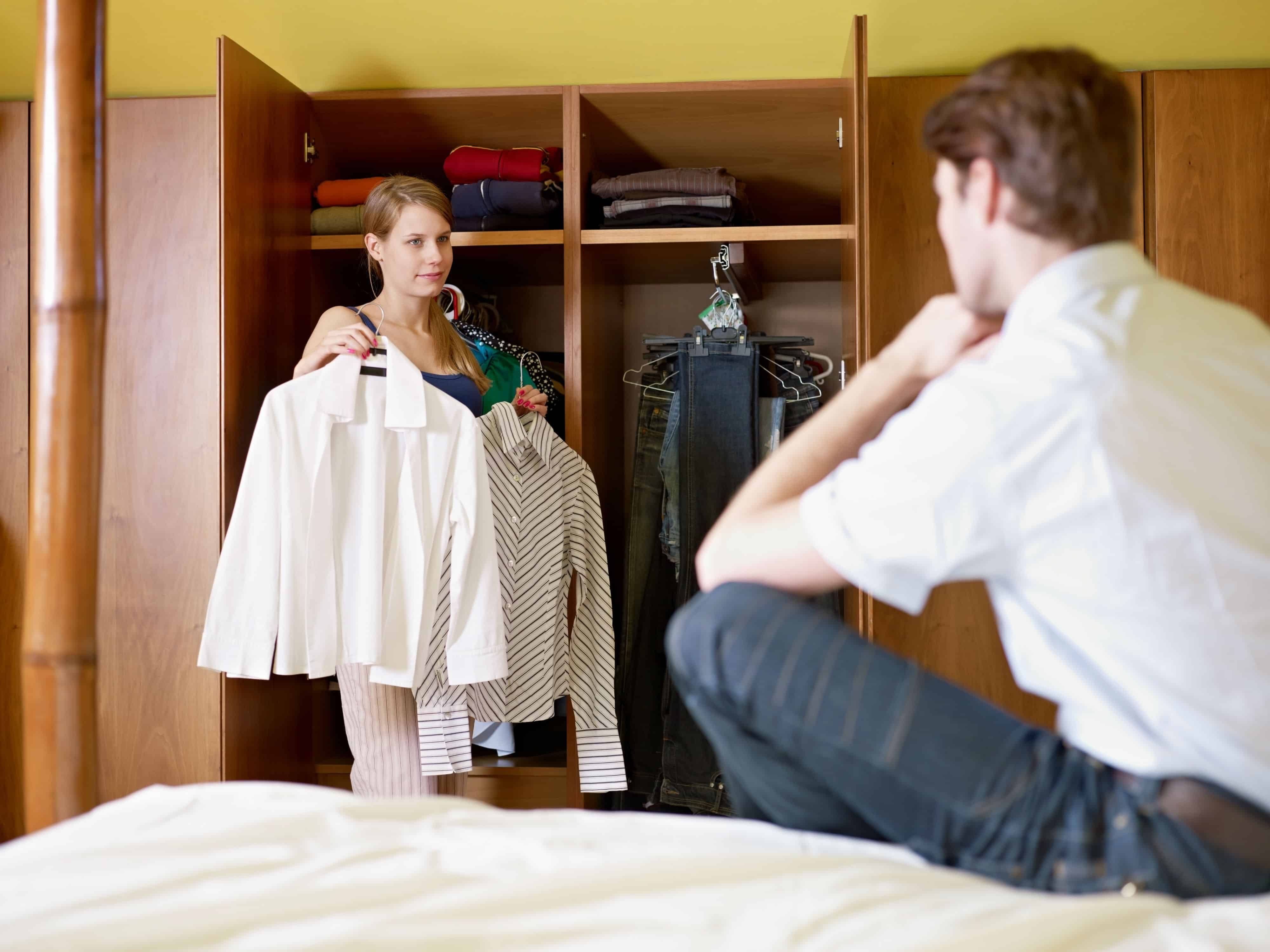A man and woman deciding what to keep in their closet.