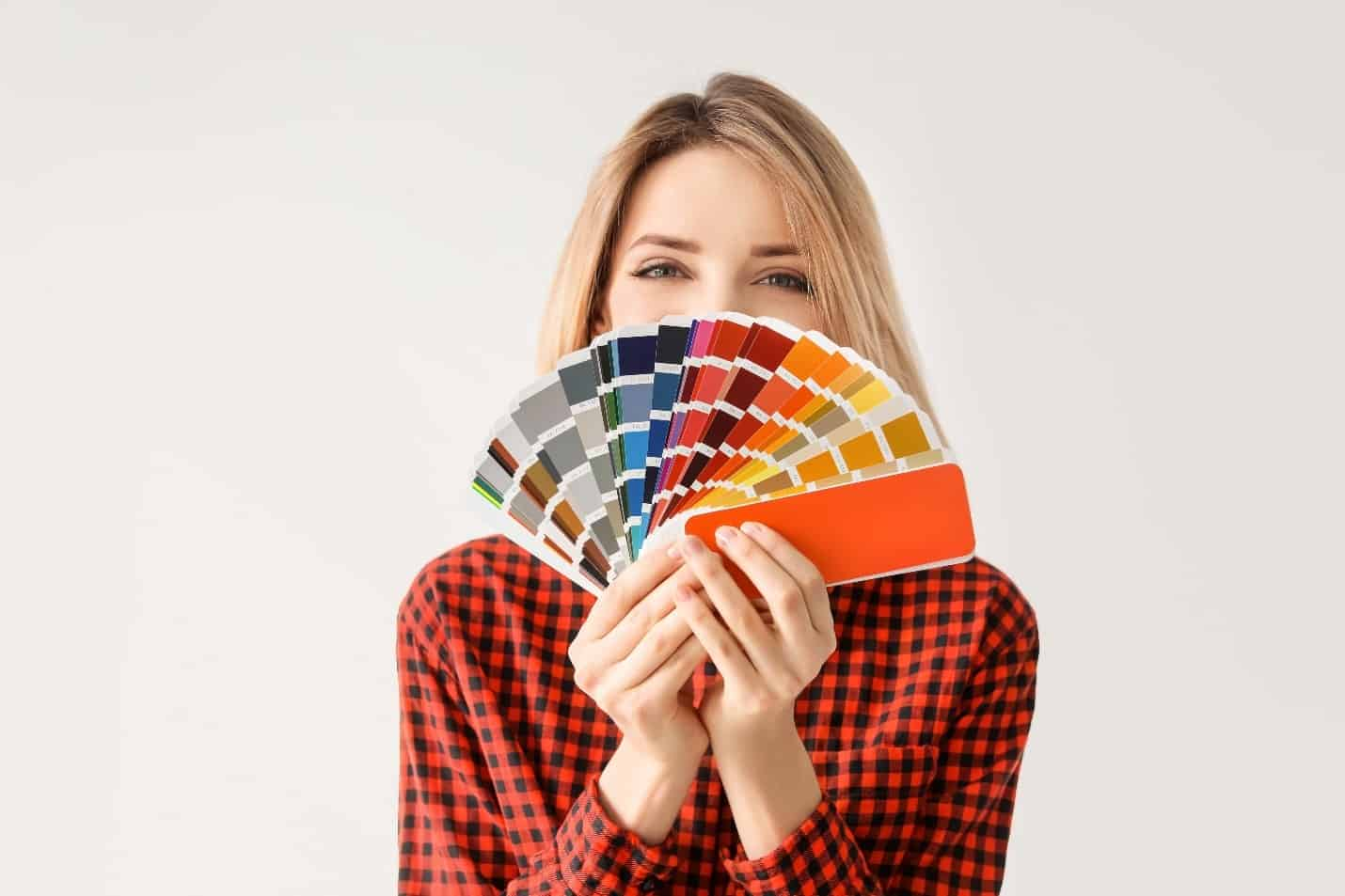 A woman holding a fan of color samples.