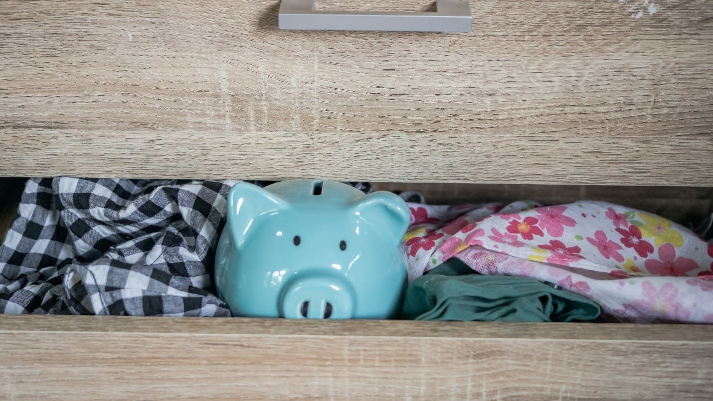 A piggy bank hiding in a clothes drawer.