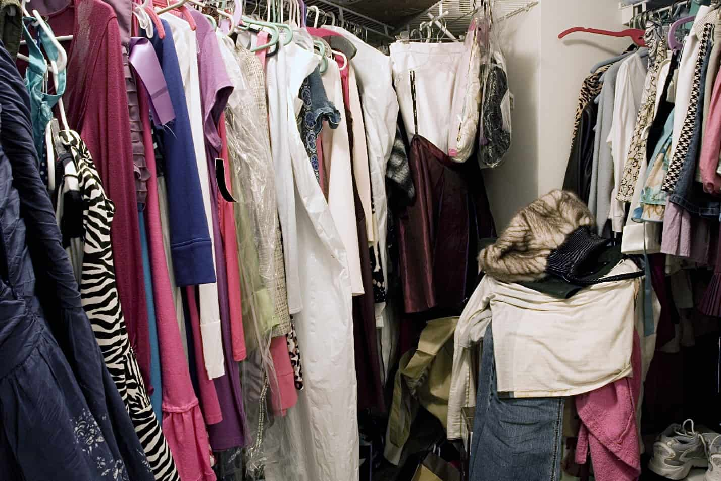 A messy closet full of clothes.