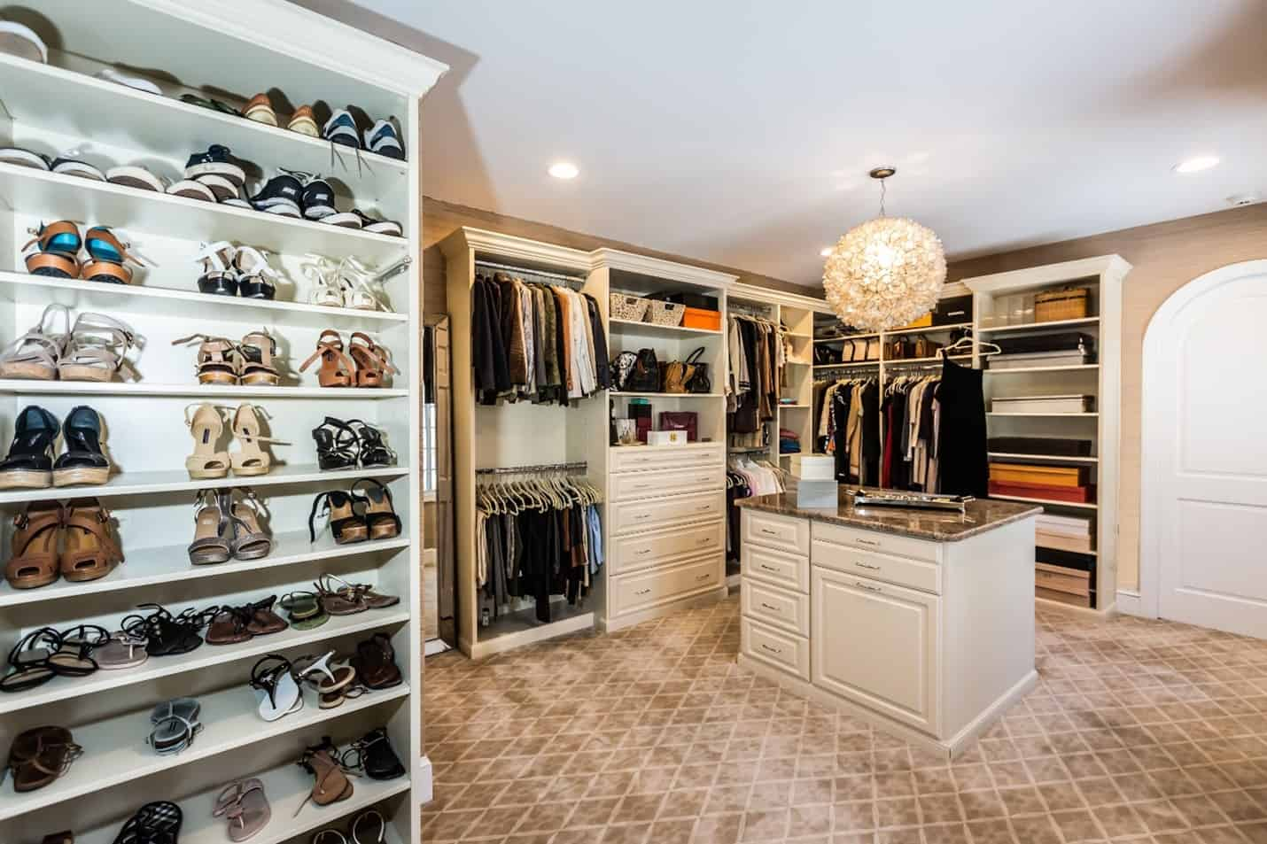 A grand walk-in closet with a shoe rack and island.
